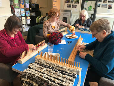 Student learning to weave on a rigid heddle loom